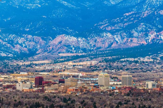 Arial view of Colorado Springs, Colorado skyline with mountains behind it.