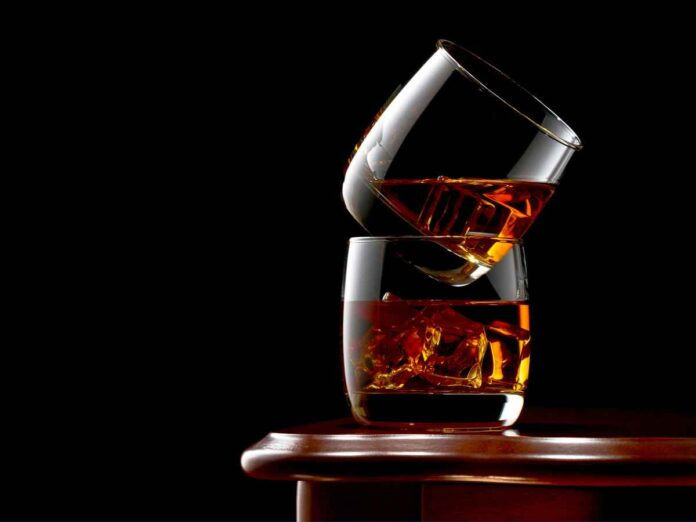 Two glasses of whiskey and ice on the wooden table. The glasses are stacked on top of each other.