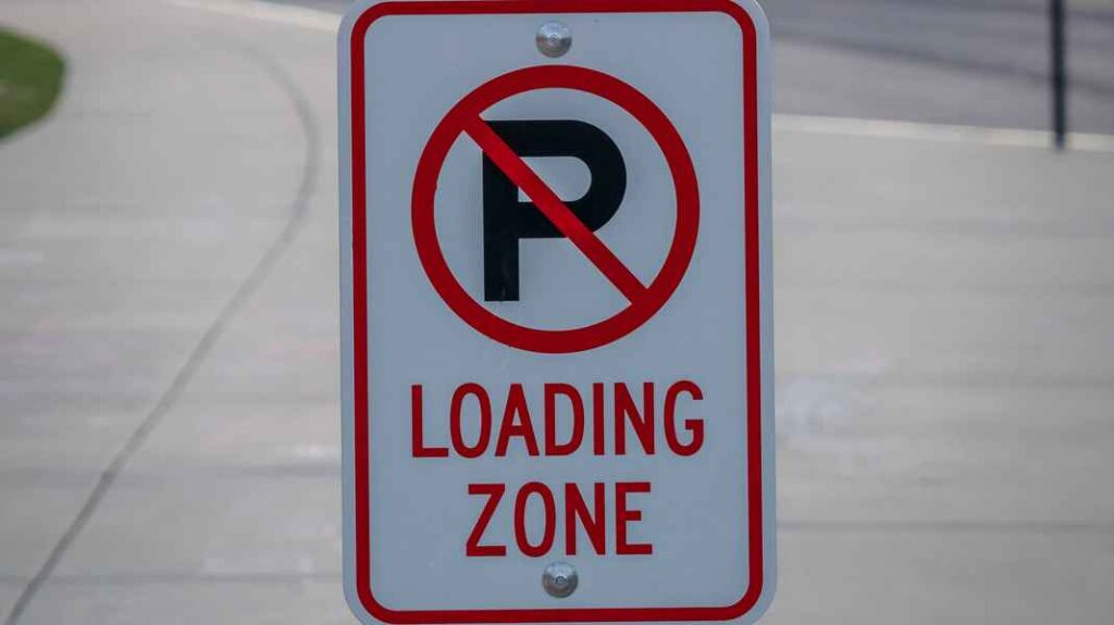 Red and white parking sign indicating no parking and loading zone.