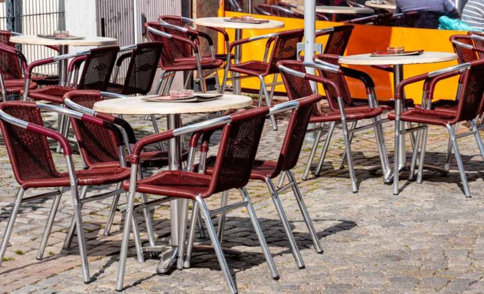 Empty cafe tables and chairs on a cobblestone patio.