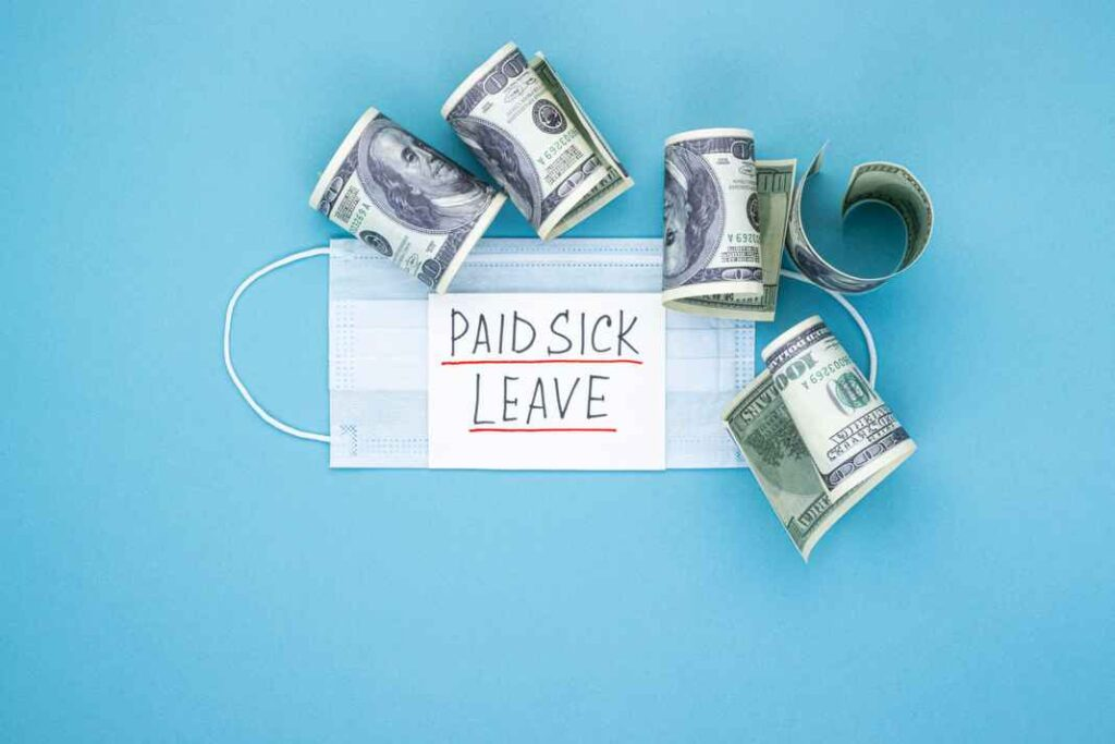 Medical mask with dollars and the words paid sick leave on a blue background. Concept of economic dependence on the COVID-19 coronavirus pandemic.