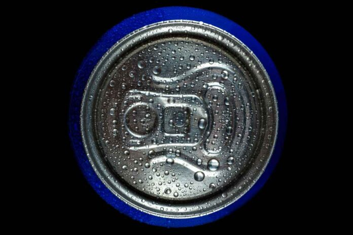 Top of an aluminum beverage can on black background.