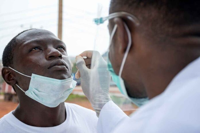 Black doctor taking nasal sample from a man.