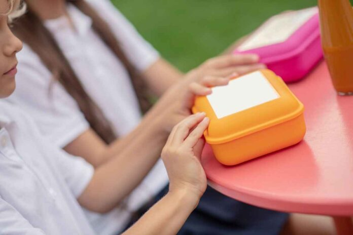 Close up of childrens' hands on pink and orange lunch boxes.