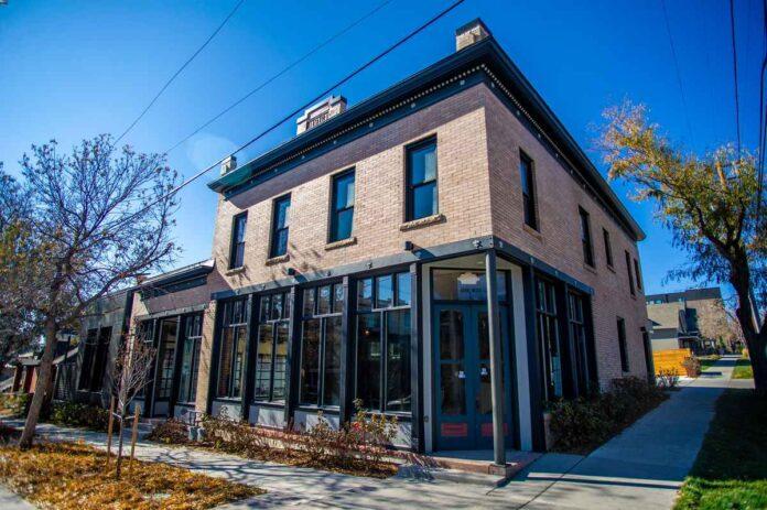 Glass front door of two-story, tan brick building.