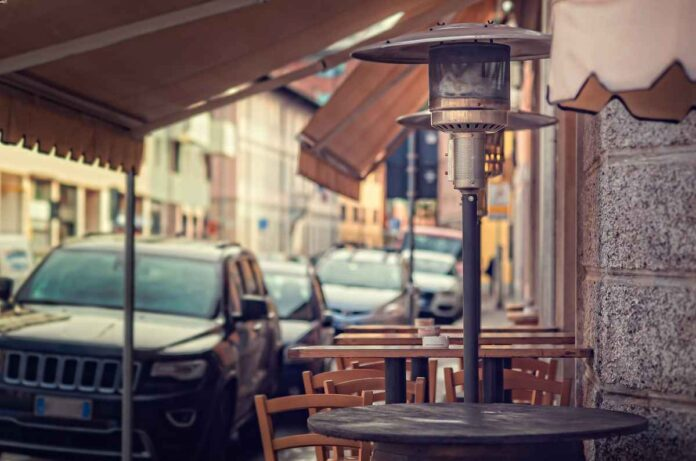 Cafe tables on a sidewalk covered by awnings with a gas mushroom heater.