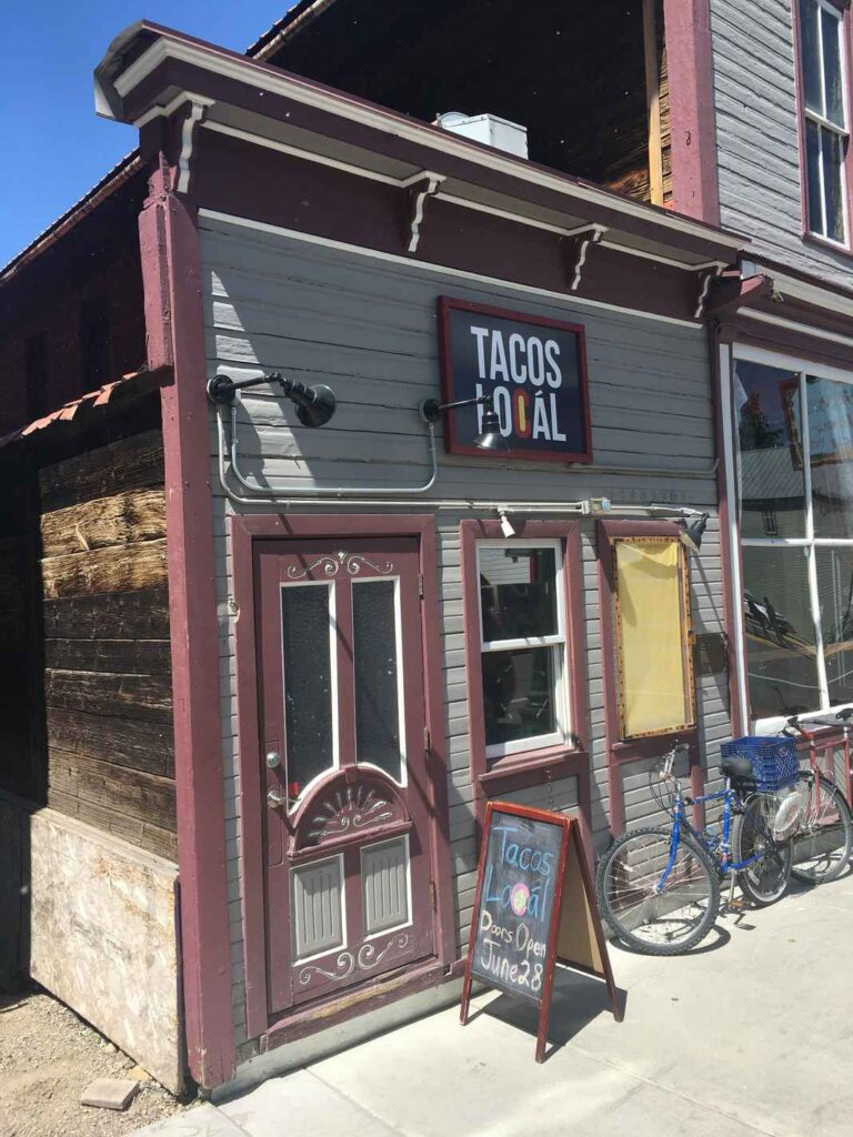 """Gray and red exterior of Tacos Locál, with a bike parked outside and sandwich board reading, """"Doors Open June 28."""""""
