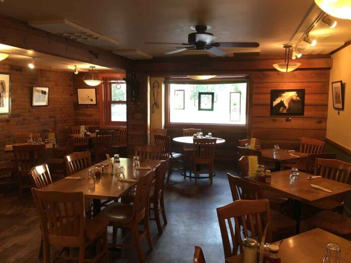 Village Smithy's dining room, with wood wall paneling, hardwood floors, and wooden tables and chairs.