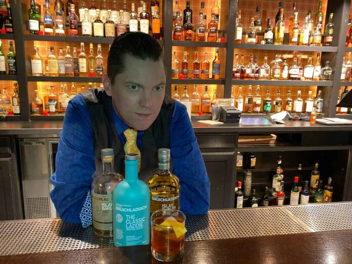 Bartender in a blue shirt standing behind a bar with a cocktail and three liquor bottles on the bar.