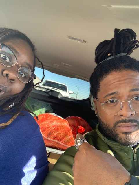 Selfie of Black man and woman with dreadlocks pointing to donated food behind them.