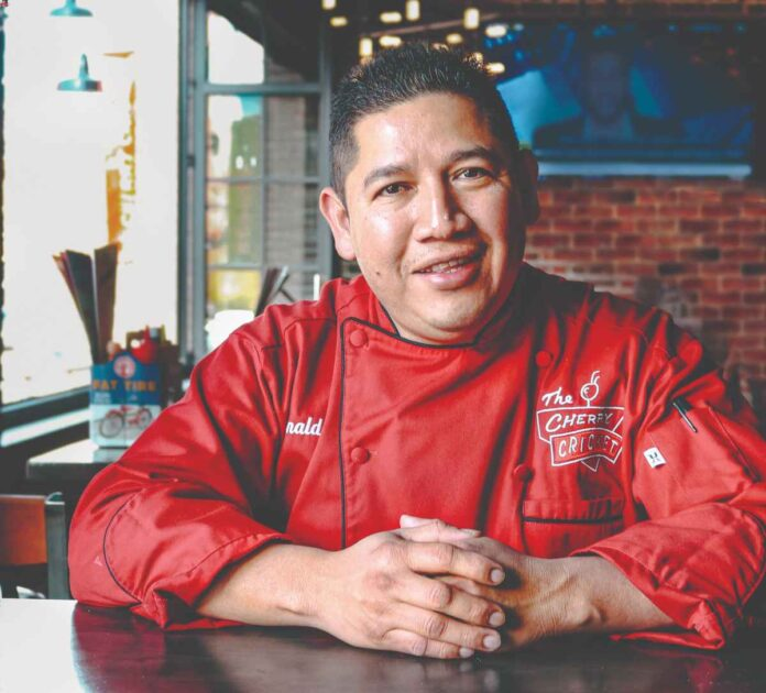 Ronaldo Munoz sitting at a table wearing a red chef's coat from the Cherry Cricket with his hands clasped in front of him.