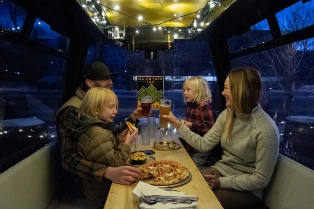 Two adults and two children sitting inside a repurposed ski gondola, smiling, eating, and drinking.