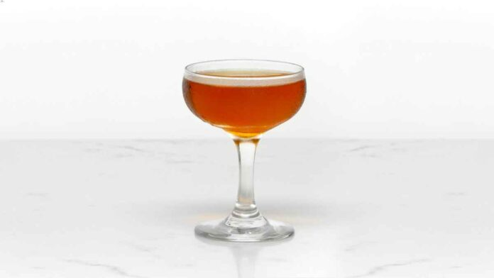 Amber beverage in a coupe glass on white background