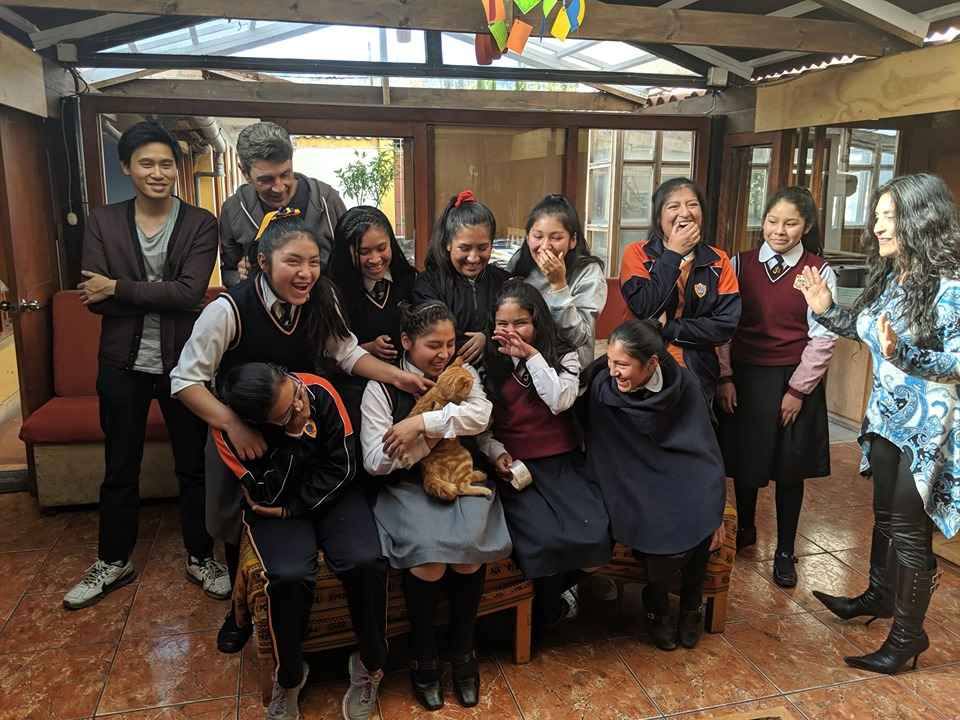 A group of eight female students in school uniforms laughing and cuddling an orange cat.