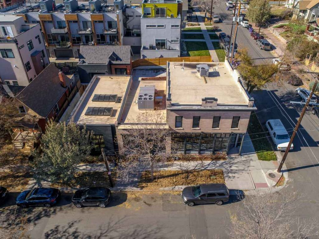 Aerial view of tan brick building on the corner of a city block