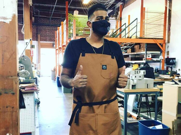 Dark-haired man standing in a workshop wearing a black face mask, camel apron and giving two thumbs up.