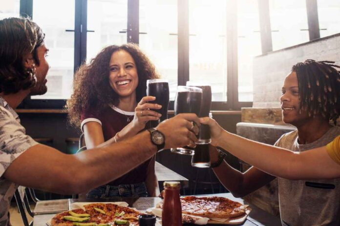 Three Black men and women toasting cold drinks with pizza on table at restaurant.