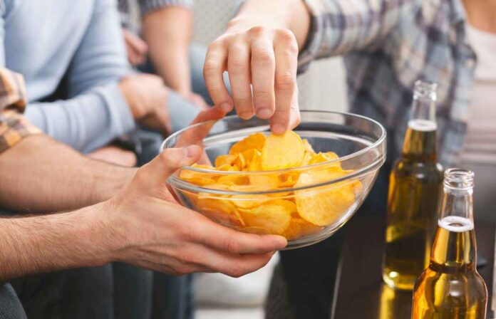 Man's hand holding a bowl of potato chips while others take chips, with beer bottles visible in corner of shot.