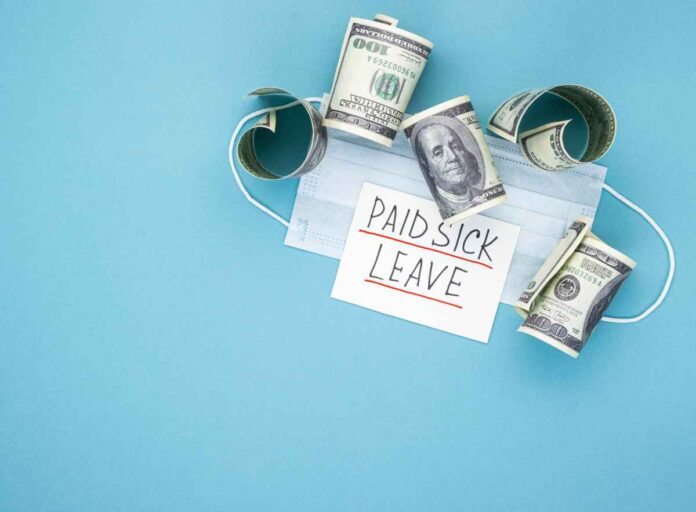 Medical mask with dollars and the words paid sick leave on a blue background.