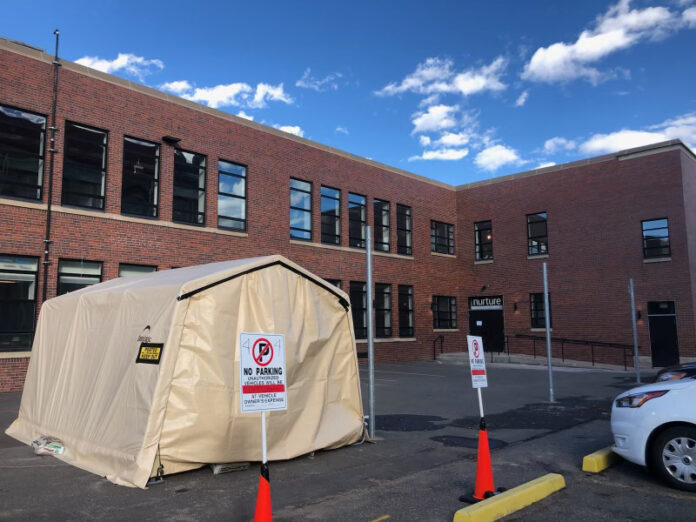 Medical tent in parking lot outside two-story brick building.