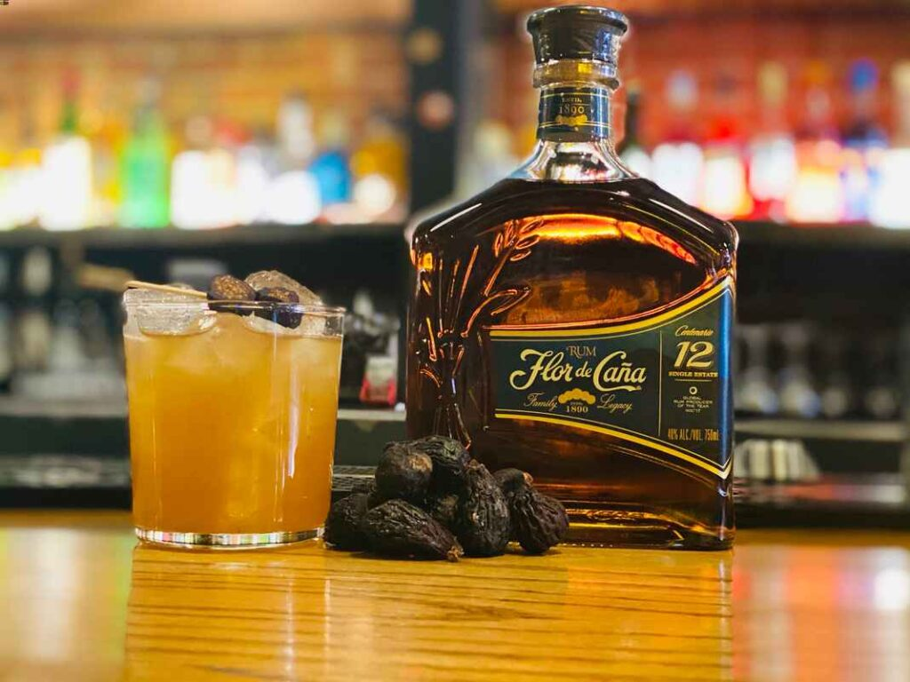 Golden liquid and ice in cocktail glass next to bottle of Flor de Cana rum and some dried figs.