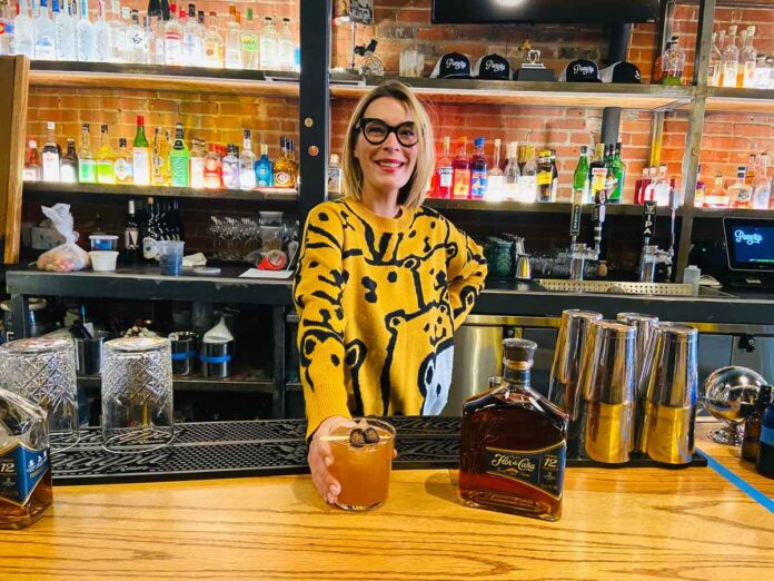 Smiling blonde woman behind a bar; golden cocktail and bottle of Flor de Cana rum sitting on the bar.