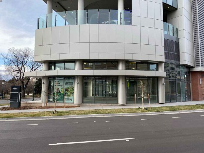 Exterior of retail space in modern gray building at intersection.