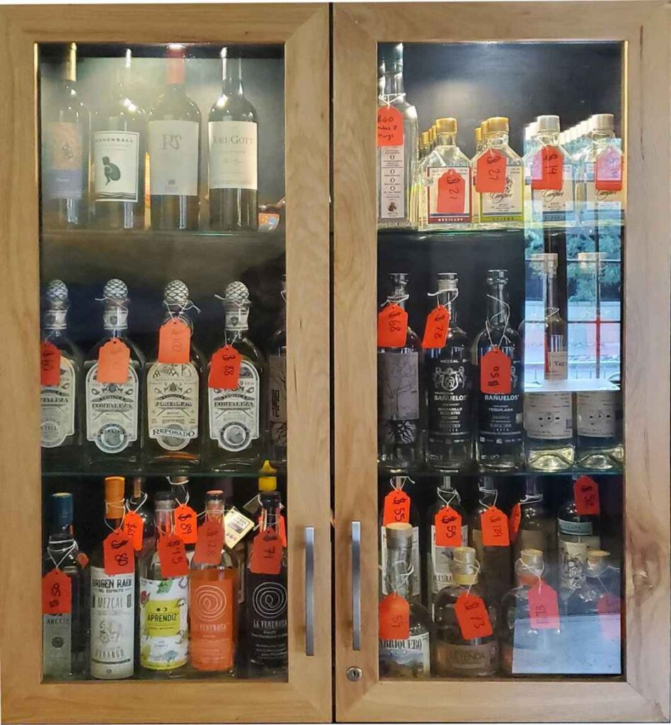 Glass cabinet doors with rows of tequila and mezcal bottles with price tags inside.
