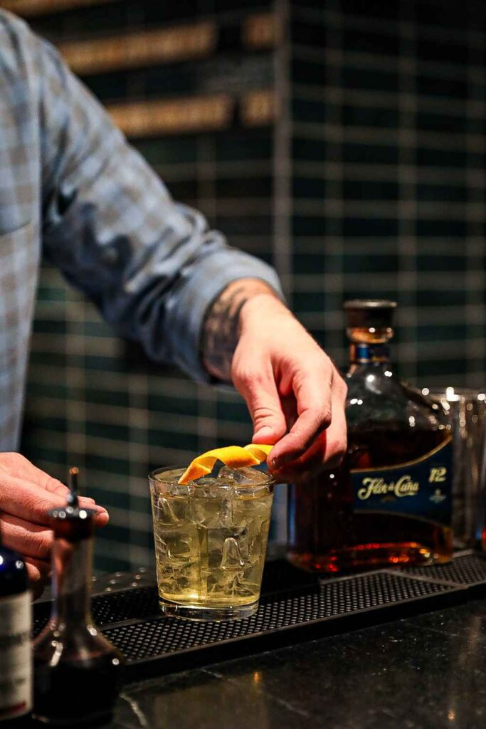 Male bartender's hands garnishing a clear amber-colored drink in a glass with orange peel. Bottle of rum in background.