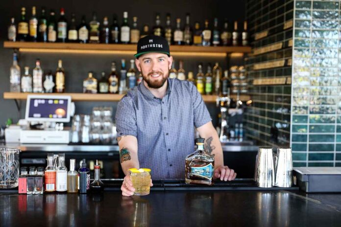 Male bartender in blue shirt and hat smiling an reaching over bar holding clear amber-colored beverage in a glass.