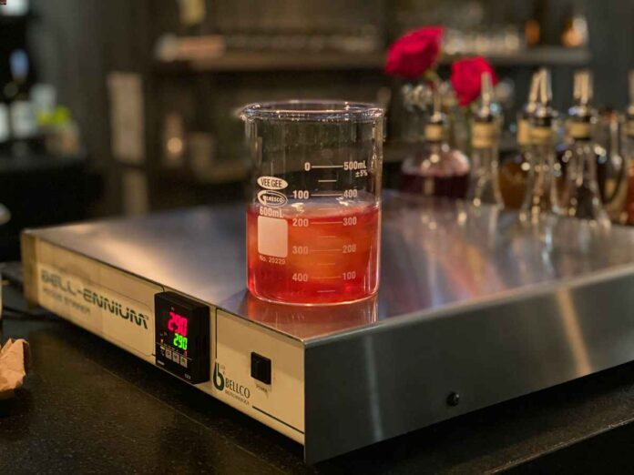 Lab beaker on magnetic stir plate filled with ice and amber liquid. Bar materials in background.