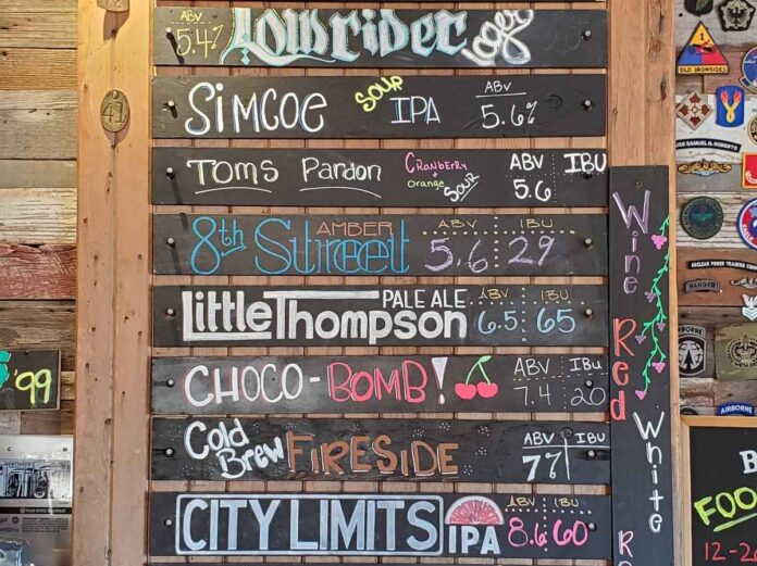 Rustic beer list with names and prices of beers written in multicolored chalk.