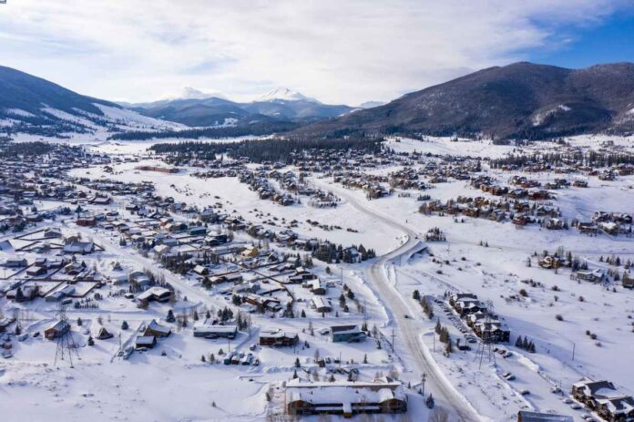 Aerial view of Keystone Colorado with snow on buildings and mountains.