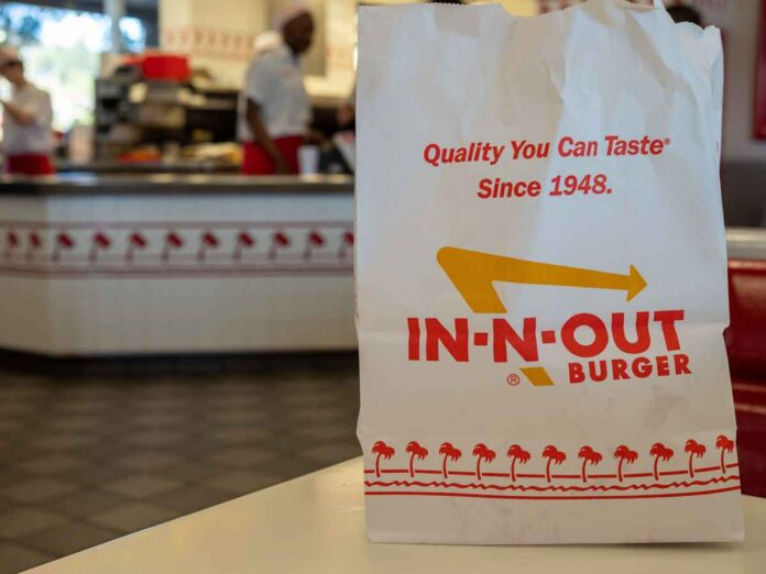 Red, white, and yellow In-n-out Burger chain bag sitting in the fast food restaurant location.