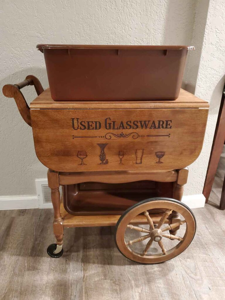 "Wooden bar cart with wheels and ""Used Glassware"" engraved on the side."