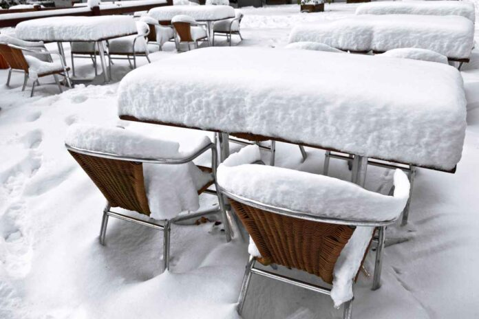 Outdoor cafe table and chairs covered in a thick layer of snow.