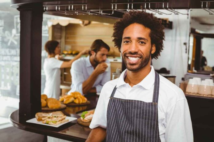 Handsome Black waiter wearing apron and smiling at camera at the coffee shop