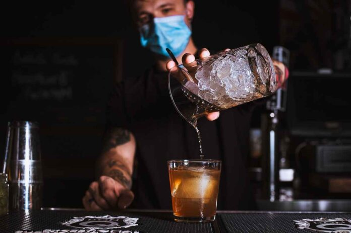 Male bartender wearing a face mask straining an amber-colored liquid into a cocktail glass.