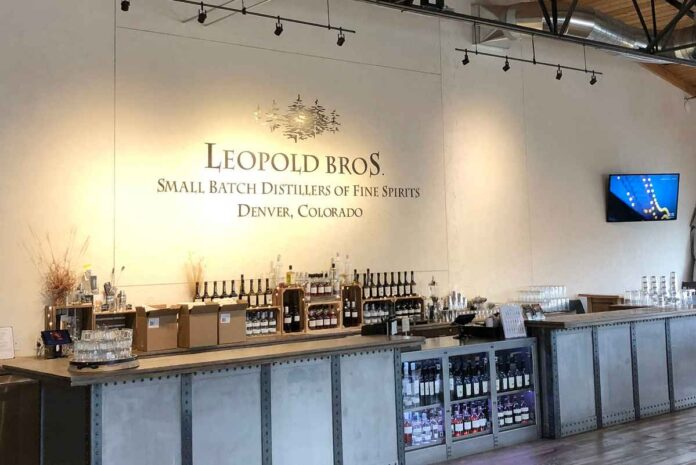 Leopold Bros. distillery tasting room with sales counter, logo on wall and AV equipment mounted on wall.