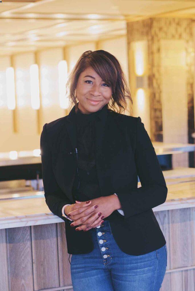 Smiling Black woman wearing black blazer and jeans.