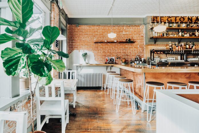 Restaurant dining room with white furniture, red brick wall, and a wooden bar with white and black barstools.