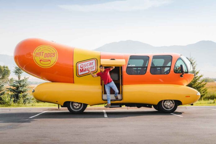 Young man wearing a facemask waving from a bus shaped like a hot dog.
