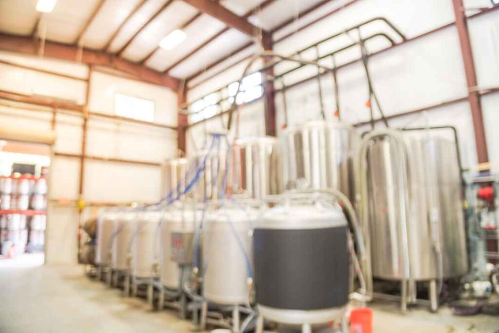 Blurry metal beer tanks, fermenters, and brewing system in a warehouse.