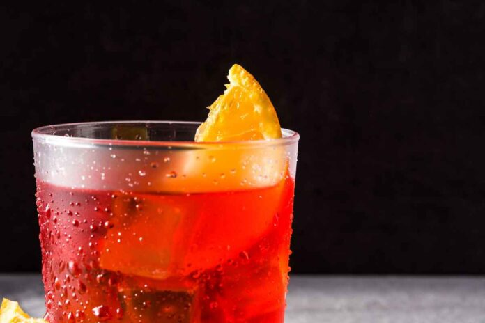 Bright red Negroni cocktail with piece of orange in glass on black background