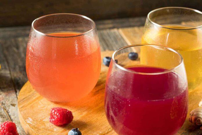 Three glasses of pink, red, and yellow alcoholic kombucha.