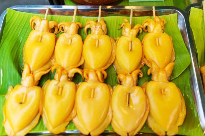 Skewered bright yellow squid ready for grilling on a bright green banana leaf.