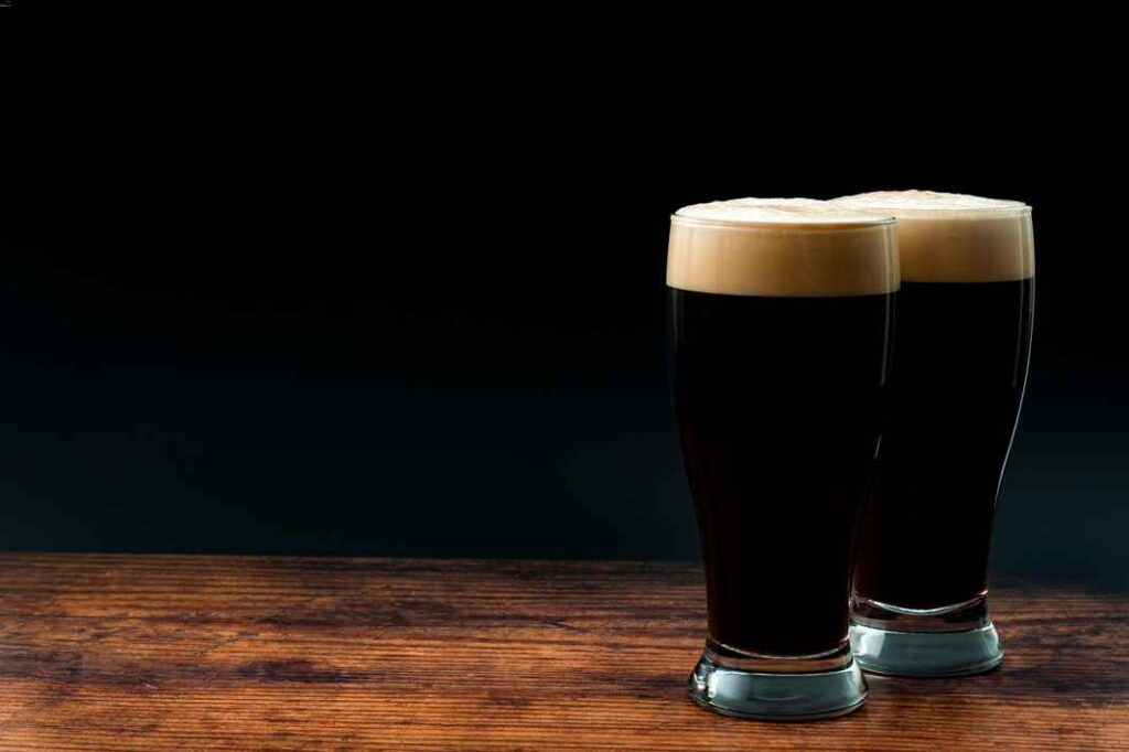 Two pint glasses filled with dark beer on wooden table with black background.