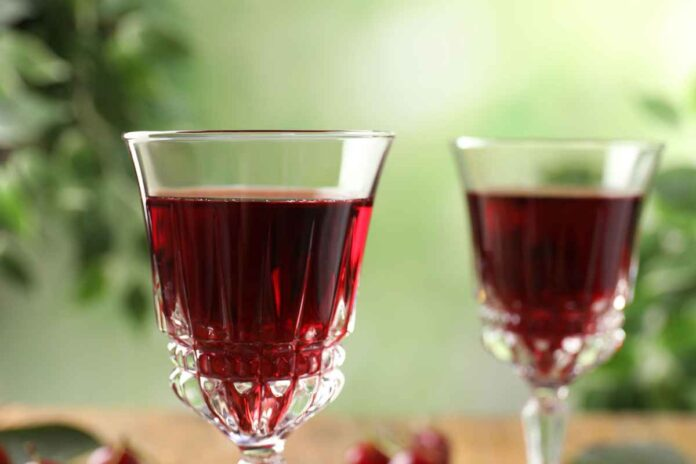 Two cordial glasses filled with red liquid against blurred green background.