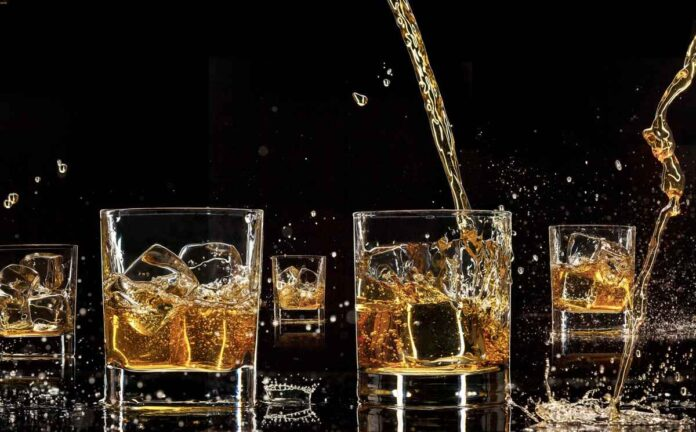 Five whiskey glasses against black background with amber liquid being poured from above and splashing outside glass.