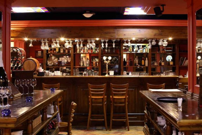 Empty pub with wooden bar, back bar, tables, and barstools.